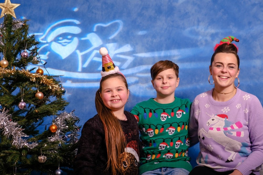 A family of 3 in Christmas jumpers and hats, next to a Christmas tree, with Santa and some Christmas presents projected behind them.