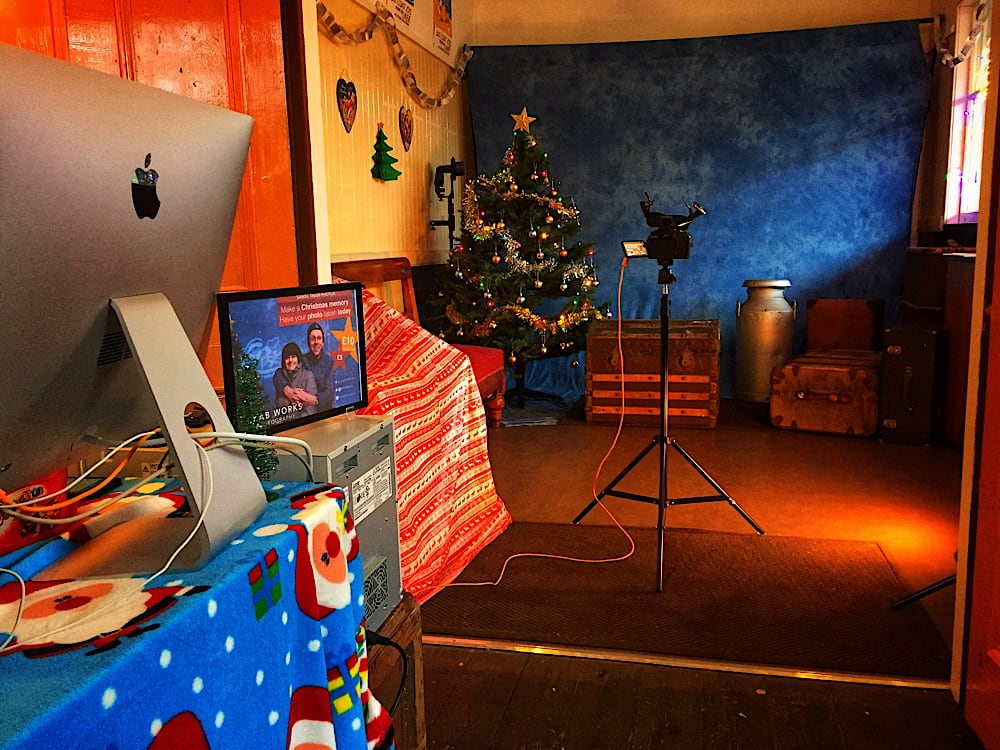 In the foreground, there is a computer on a table with a blue Santa tablecloth over it. In the background, a camera is pointing to a blue backdrop, in front of it is a Christmas tree and various suitcases to sit on.