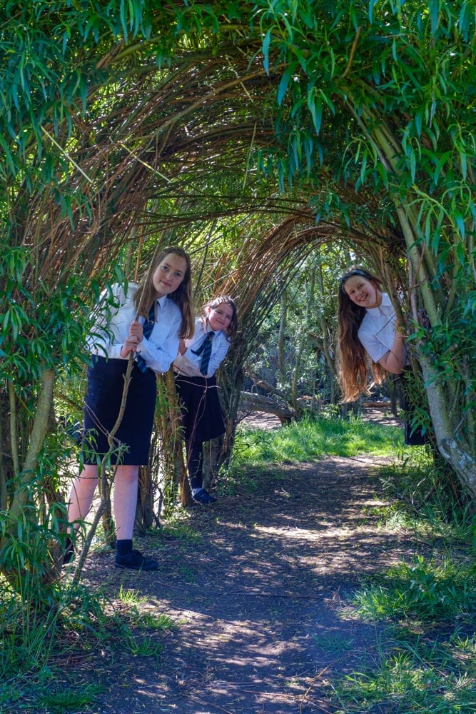 A group of 3 schoolgirls peek out from behind willow which makes an arch over a path.