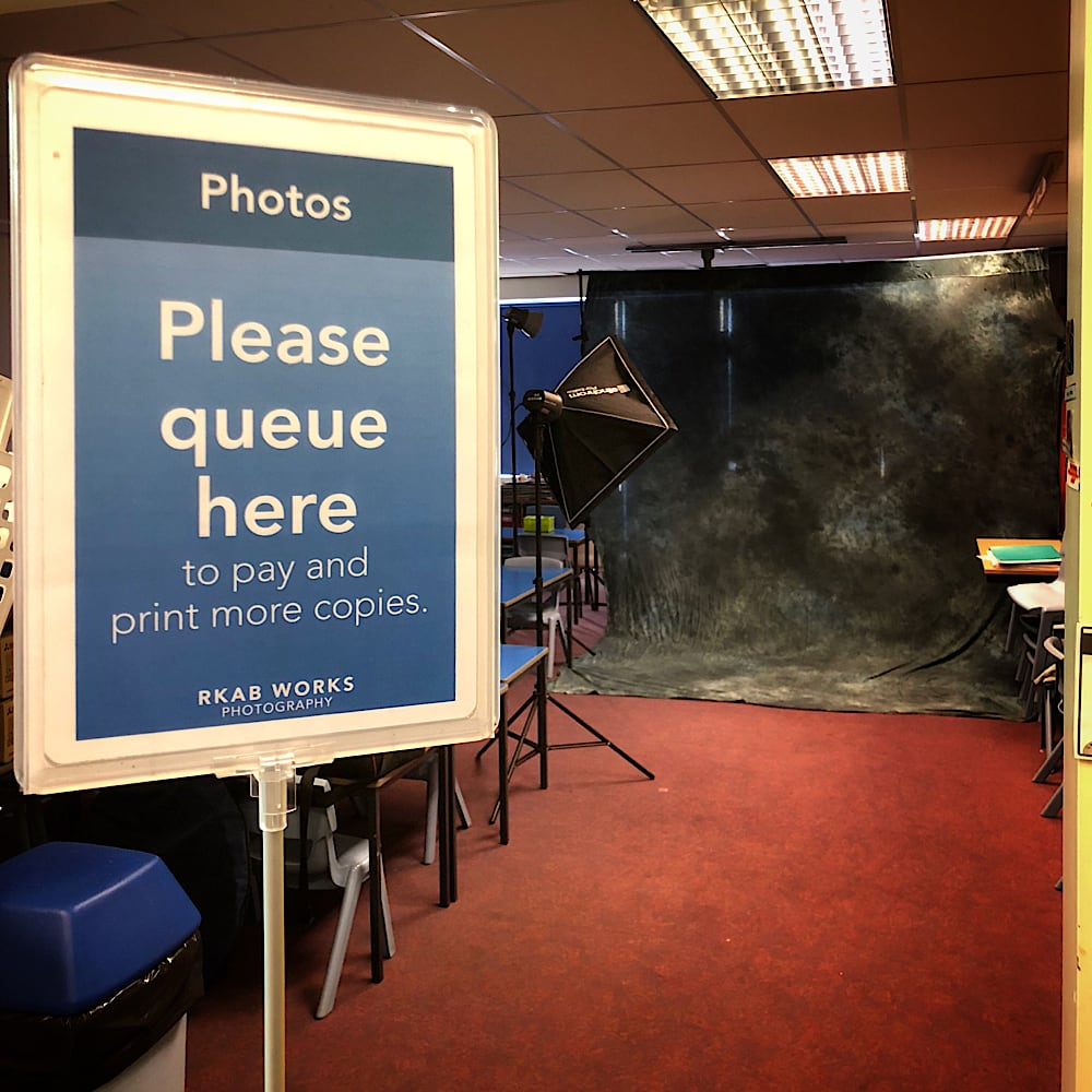 "In the foreground, a sign advises the reader to ""Queue here to pay and print more copies."" In the background, a large photography light points to a dark background."