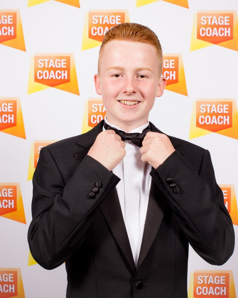 A young boy dressed in a tuxedo adjusts his bow tie, on a backdrop with the logo for 'Stagecoach'.