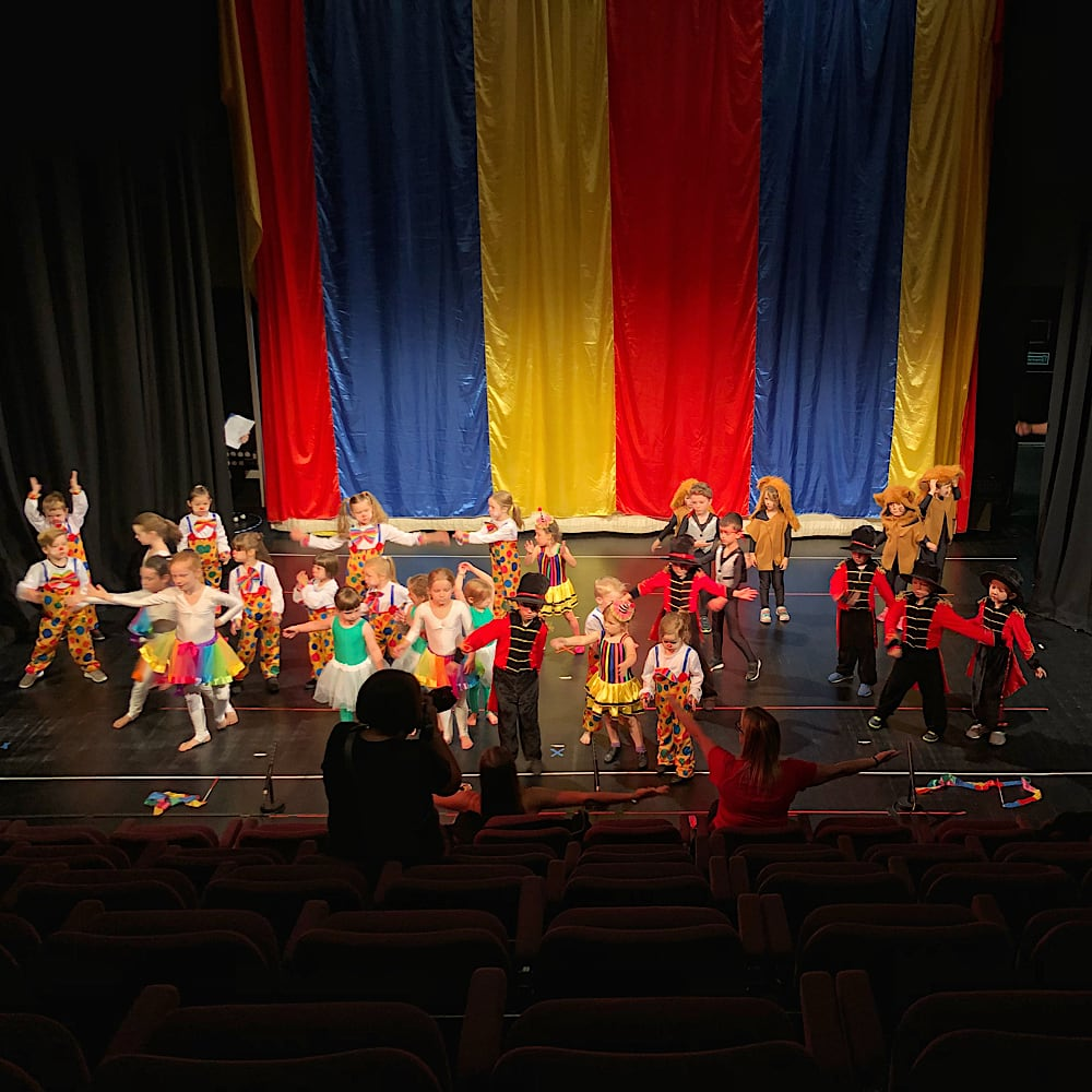 A large group of preschool children are dressed in circus costumes and dancing around a stage with a brightly coloured stripy background.