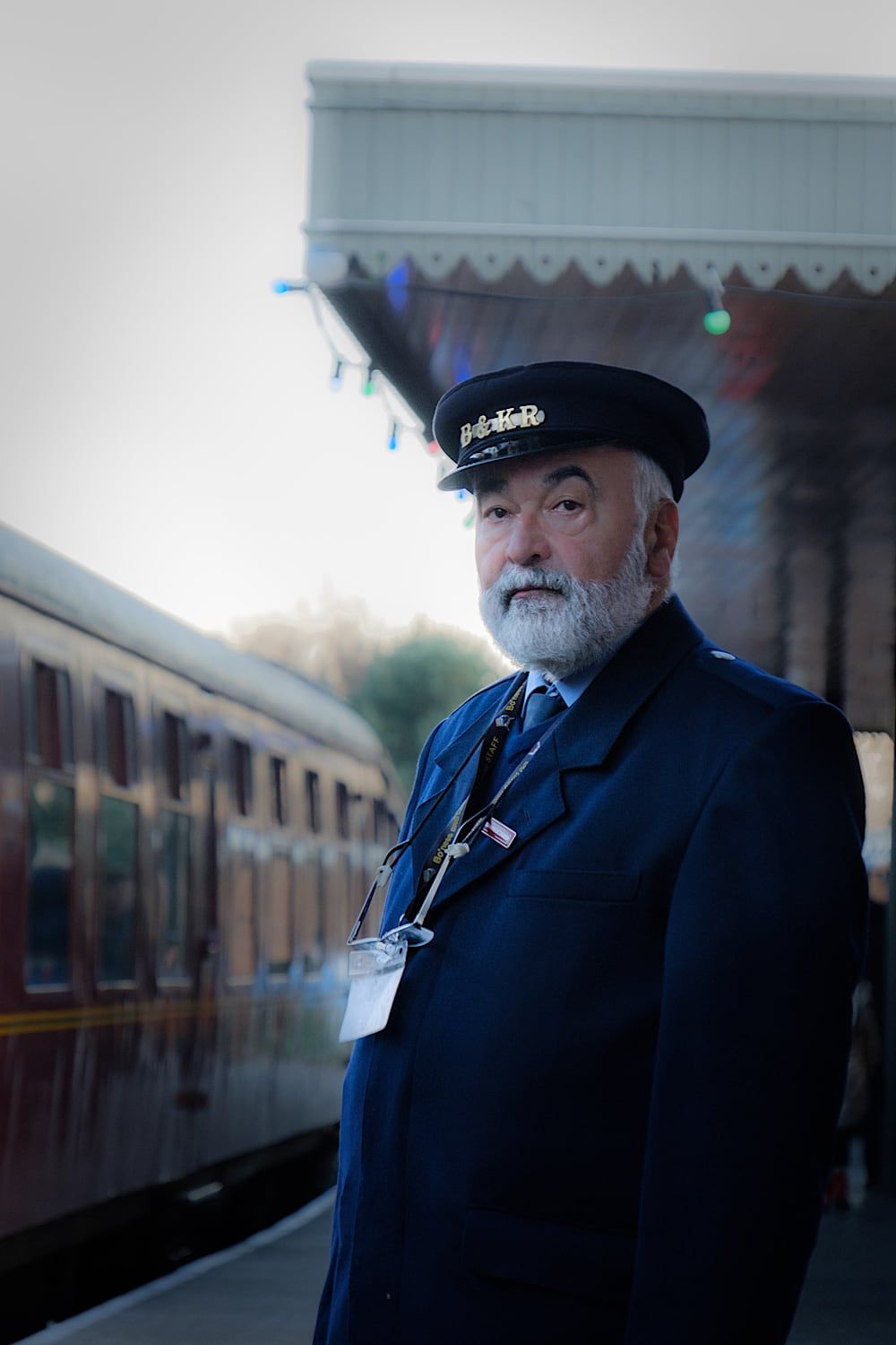 A bearded man in old-fashioned Station Master uniform looks towards the camera on the platform, with an old style train carriage in the background.