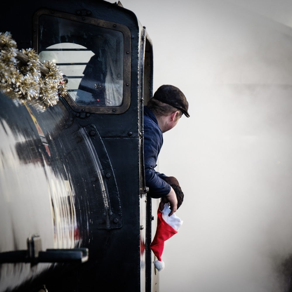 A train driver looks out of the side of a steam engine window. Steam fills the background.