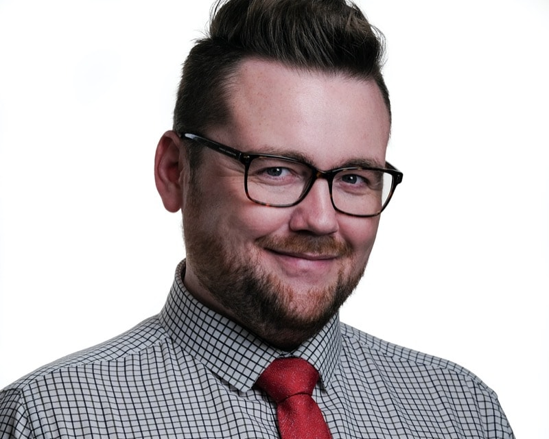 Headshot of a man with a short beard and glasses with a rectangular frame. He has a checked shirt with a red tie.